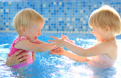 Happy children in swimming pool. Two happy children girl in swimming pool royalty free stock photos