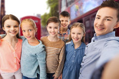 Happy children talking selfie over london city. Childhood, travel, tourism, technology and people concept - happy children talking selfie over london city street Stock Image