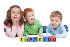 Happy children with thankyou kids letter blocks. Three children lying with saying thankyou with kids letter blocks. Isolated on white royalty free stock photography