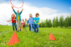 Happy children throw colorful hoops on cones. While competing with each other during summer sunny day stock photography