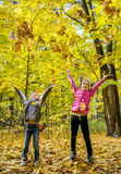 Happy children throwing leaves up Stock Photo