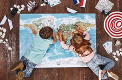 Where would you like to visit Children looking at world map, while lying on it, near travel items stock image