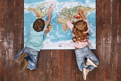 Discover the World. Children lying on world map, looking at it royalty free stock image