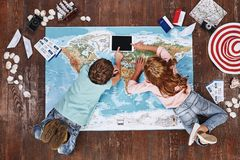 To travel is to discover. Children lying on world map near travel items and touch iPad royalty free stock photography