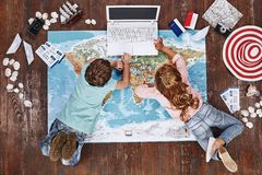Let`s check. Children lying on world map near travel items and play on toy computer stock photo