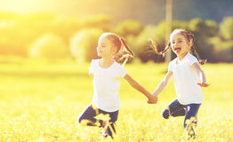 Happy children twins sisters run and play outdoors Stock Photography