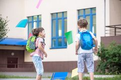 Happy children - two boys friends with books and backpacks on the first or last school day. stock images