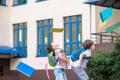 Happy children - two boys friends with books and backpacks on the first or last school day. royalty free stock images