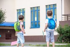 Happy children - two boys friends with books and backpacks on th stock images