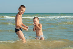 Happy  Children - two boys having fun on the beach Stock Image