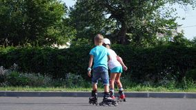 Happy children, two boys of seven, rollerblading, a hot summer day. Slow motion.  stock video