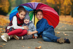 Happy children under rainbow umbrella Royalty Free Stock Image