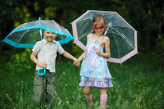 Happy children under umbrella in park Stock Image