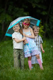 Happy children under umbrella in park Stock Photos