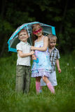 Happy children under umbrella in park Royalty Free Stock Images