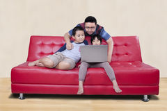 Happy children use laptop with dad Stock Photography