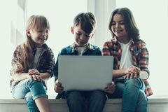 Happy Children Use Laptop Sitting on Windowsill royalty free stock photography