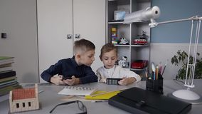 Happy children using smart phone together browsing online. Two boys sitting at a table at white room laughing at funny. Internet joke online smart phone having stock footage