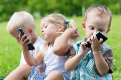 Happy children using smartphones Royalty Free Stock Photography