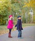 Children walking in beautiful autumn park on warm sunny fall day. Happy children walking in beautiful autumn park on warm sunny fall day Royalty Free Stock Images