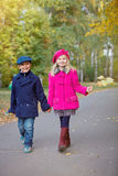 Children walking in beautiful autumn park on warm sunny fall day. Happy children walking in beautiful autumn park on warm sunny fall day Royalty Free Stock Image