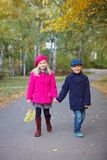 Children walking in beautiful autumn park on warm sunny fall day. Happy children walking in beautiful autumn park on warm sunny fall day Royalty Free Stock Photos