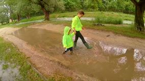 Happy Children Walking In Puddles In Park. The shot captured in green park at flood time - happy girl and little boy in rubber boots and bright jackets playing stock video footage