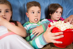 Happy children watching movie at home Stock Photography