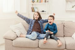 Happy children watching TV at home. Happy children watching cartoon on tv at home, brother and sister having rest without parents, copy space Royalty Free Stock Photos