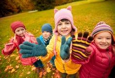 Happy children waving hands in autumn park Stock Photography