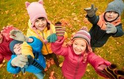 Happy children waving hands in autumn park Stock Images