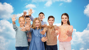Happy children waving hands over blue sky Royalty Free Stock Photos