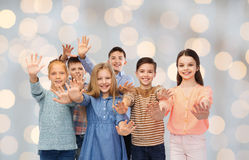 Happy children waving hands over holidays lights Royalty Free Stock Photos