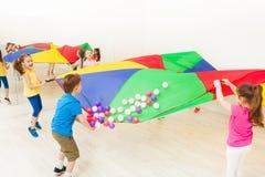 Happy children waving parachute full of balls Stock Photos
