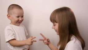 Happy children play game rock paper scissor on white background, smile and laugh stock video footage