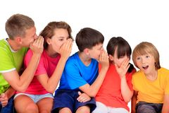 Happy children whispering. Group of five different aged children whispering secret from oldest to youngster, white background royalty free stock photography