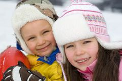 Happy Children in Winter. A cute boy and girl dressed in winter clothes, smiling and enjoying being outside in the cold Royalty Free Stock Photo
