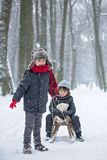 Happy children in a winter park, playing together with a sledge. While snowing. Childhood happiness concept stock photos