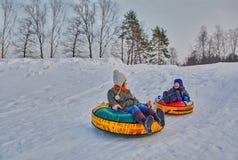 Happy children on a winter sleigh ride Stock Photo