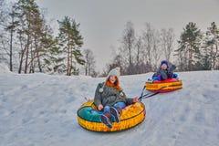 Happy children on a winter sleigh ride Stock Photos