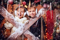 Happy children in yard. A portrait of children on the porch of their house together. Merry Christmas, happy New Year. Yard with christmas lights and decorations stock images