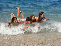 Happy childrens enjoy on waves. Cool young boy and girls (children - best friends, brother and sisters) have a summer fun  floating - riding a waves at Croatia Royalty Free Stock Image