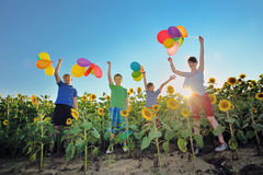 Happy childrens jumping on meadow with balloons Stock Images