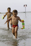 Happy childs play into sea with watergun, vacation in Italy Stock Photography