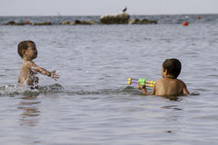 Happy childs play into sea with watergun, vacation in Italy Royalty Free Stock Photo