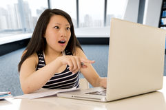 Happy chinese asian woman working and studying on her computer sitting at modern office desk smiling cheerful Royalty Free Stock Photos