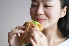 Happy Chinese beauty girl eat hamburger closeup, blank white background. Fast food, easy to make , but if you eat too much, you will get fat, it is not a healthy Royalty Free Stock Photography