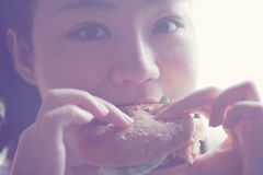 Happy Chinese beauty girl eat hamburger closeup, blank white background. Fast food, easy to make , but if you eat too much, you will get fat, it is not a healthy Stock Photos