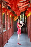 Happy Chinese bride in red cheongsam at traditional wedding day. Chinese bride in red cheongsam at wedding day , hold red oiled paper umbrella, climb stairs Royalty Free Stock Photos
