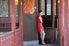 Happy Chinese bride in red cheongsam at traditional wedding day. Chinese bride in red cheongsam at wedding day , hold red oiled paper umbrella, climb stairs Royalty Free Stock Photo